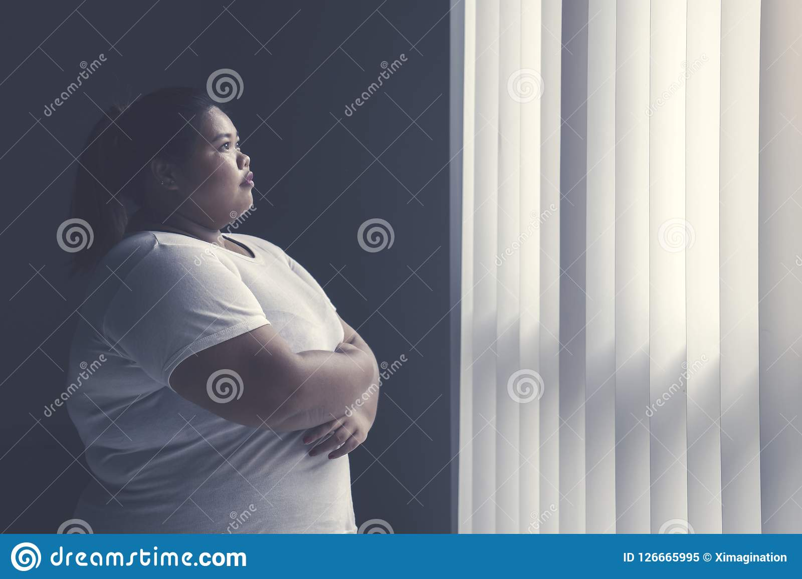 Obese woman daydreaming by the window. Image of obese woman crossed her hands while daydreaming by the window Royalty Free Stock Photo