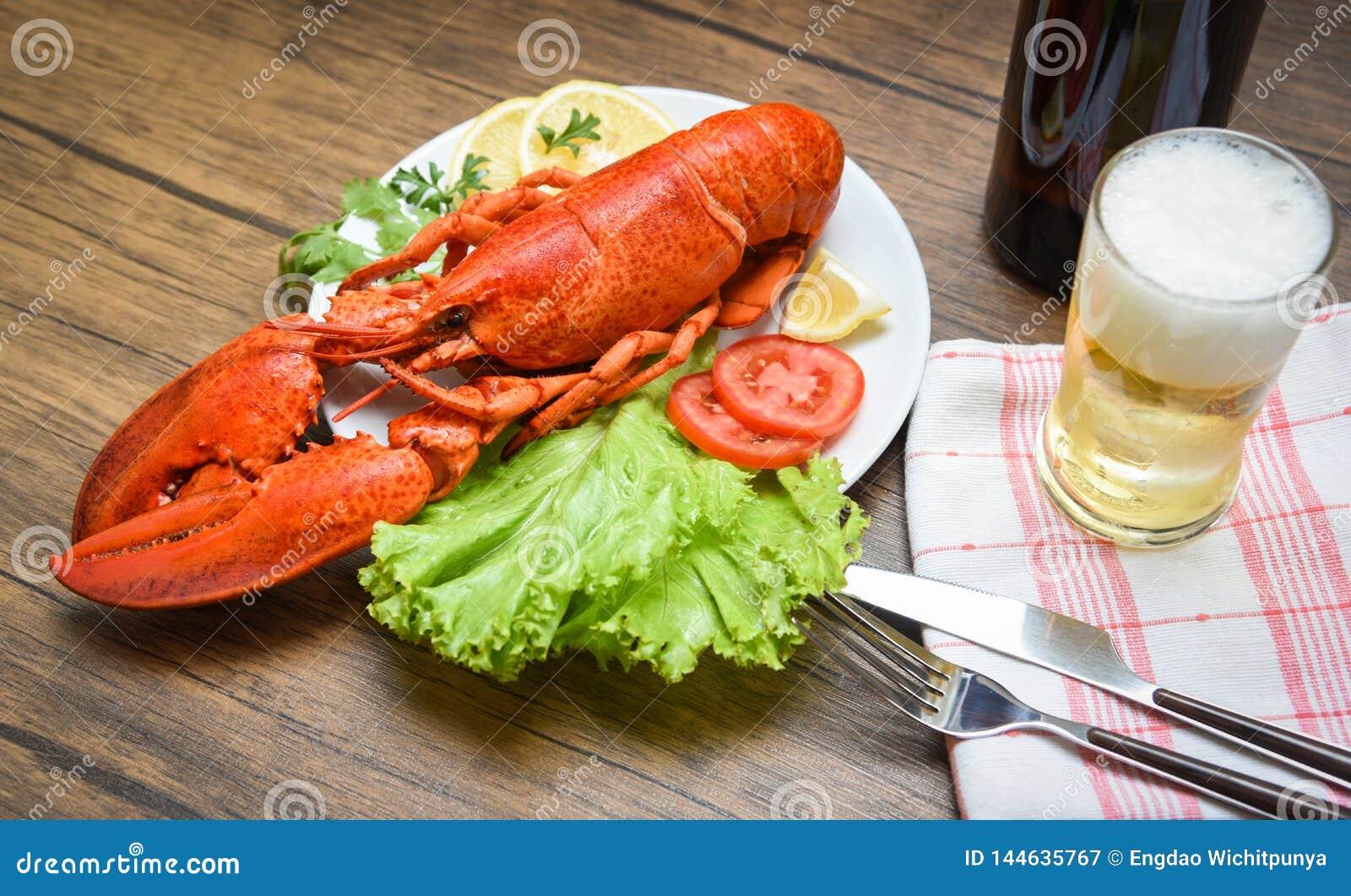 Obiadowy owoce morza homar dekatyzował na półkowym owoce morza z cytryny sałaty sałatkowym warzywem i szkłem na stole pomidorowym