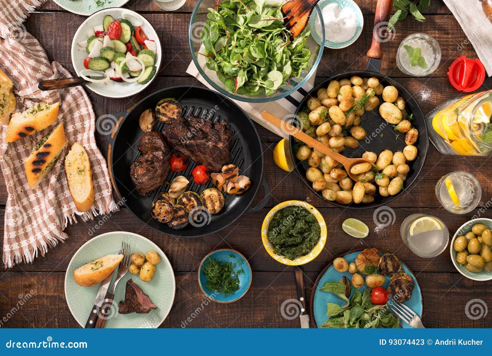 Obiadowy stół z piec na grillu stkiem, warzywa, grule, sałatka, sn