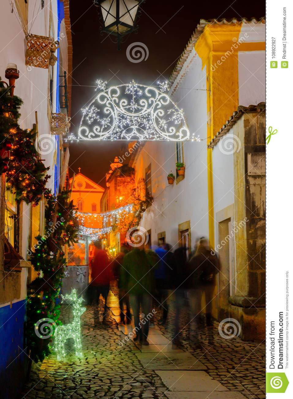 obidos portugal december 27 2017 view of an alley in the old town with local businesses saint james church and christmas decorations in obidos - Christmas Decorations For Businesses
