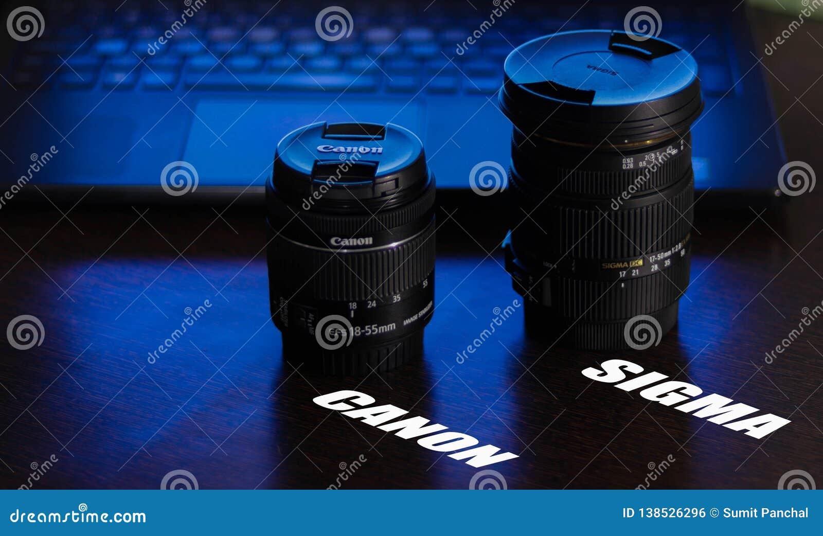 Objectifs de caméra Canon et sigma sur la table avec la lumière violette bleue du fond, le clavier d ordinateur portable et le pa