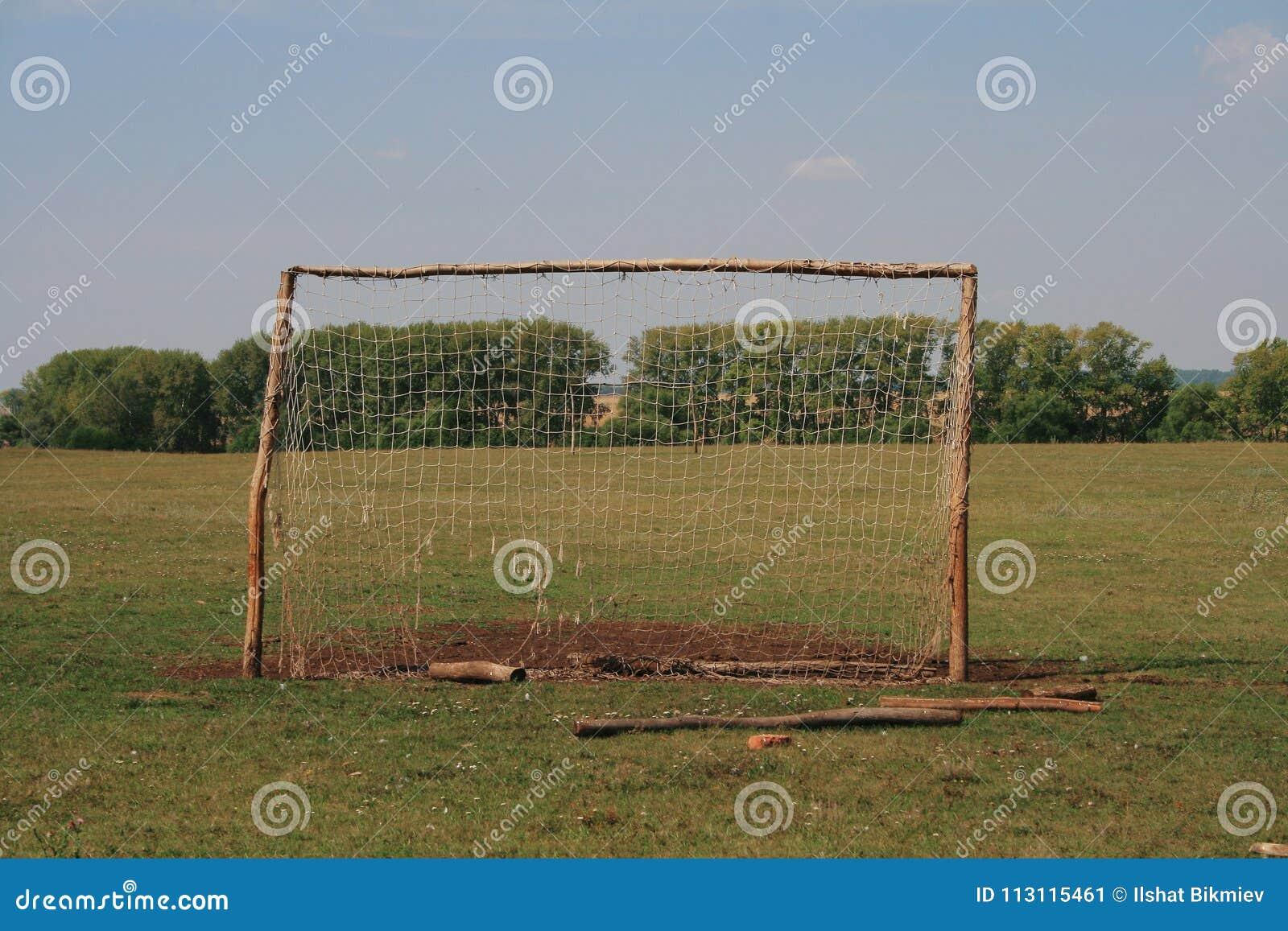 Objetivo velho do futebol para o mini futebol no gramado pisado na zona da floresta