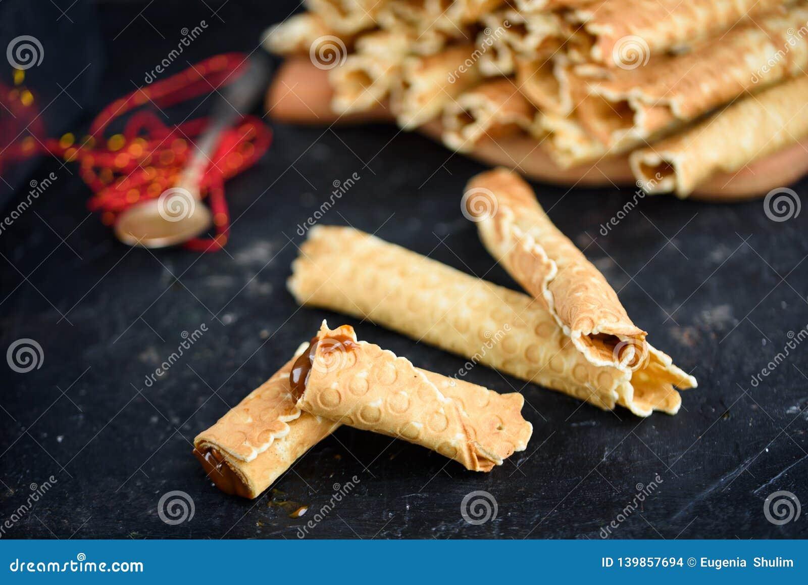 Oblatenrollen, geschmackvoll und wohlriechend, mit gekochter Kondensmilch auf einer schwarzen Tabelle