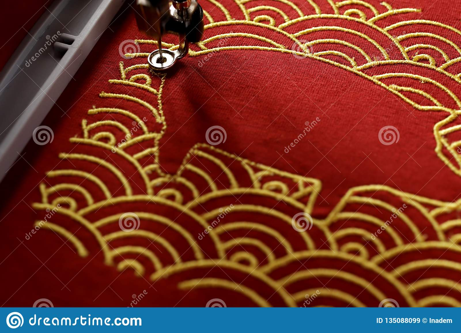 Pig embroidery framed by traditional shell pattern with gold on red fabric in festive light mood - chinese new year concept