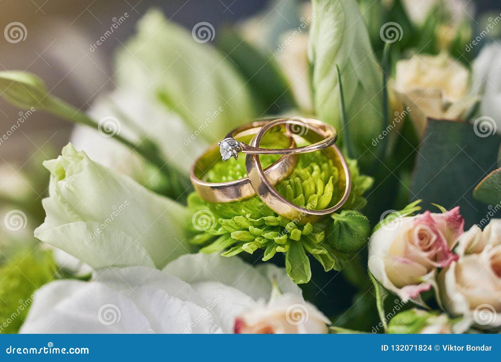 Obrączki ślubne kłamają na pięknym bukiecie jako bridal akcesoria