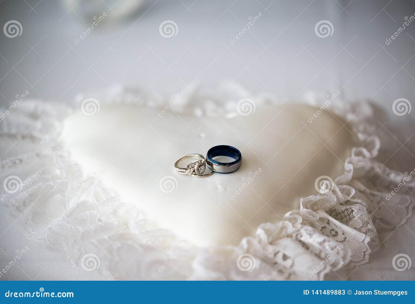Obrączki ślubne na białego serca kształtnej poduszce