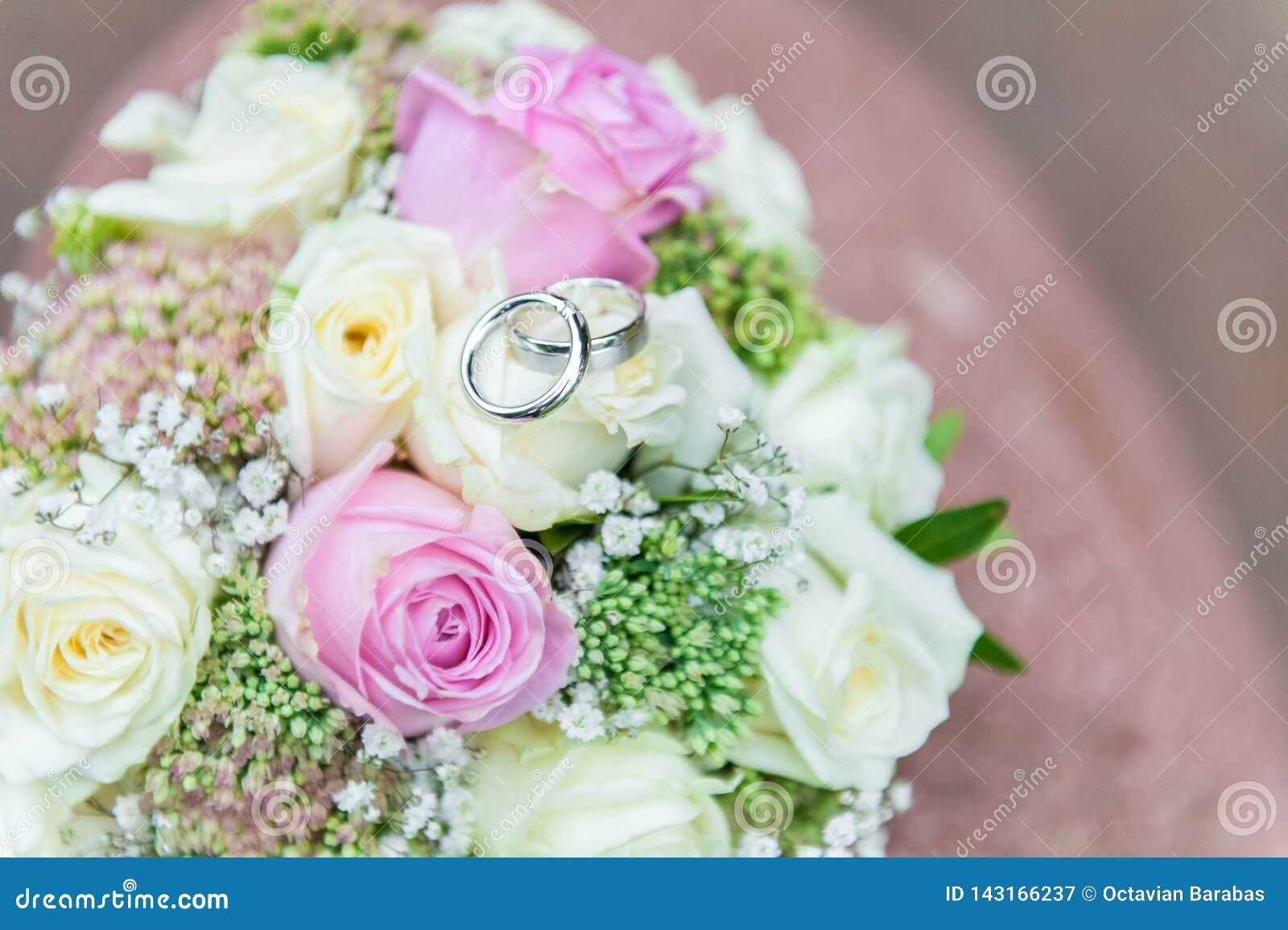 Obrączki ślubne na jaskrawym kwiatu bukiecie