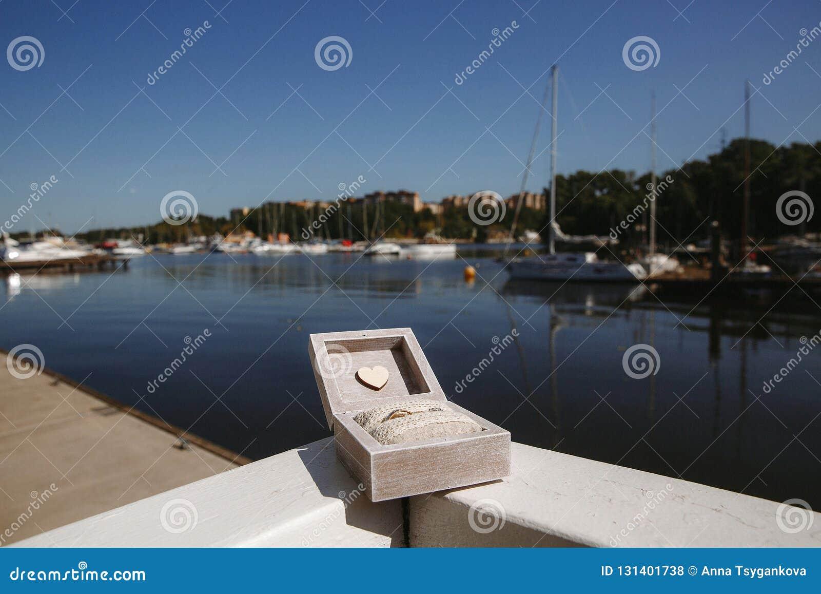 Obrączki ślubne w drewnianym pudełku na tle biali jachty w jachtu klubie