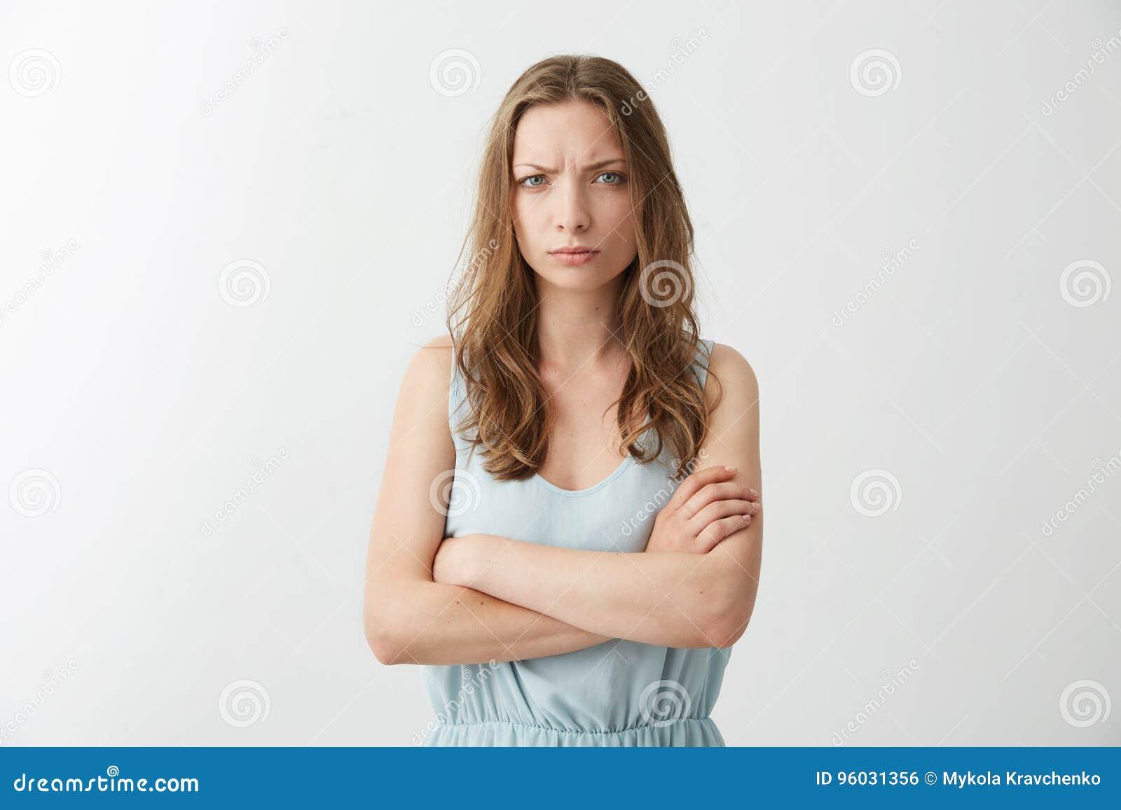 Obrażająca nierada młoda dziewczyna marszczy brwi patrzejący kamerę z krzyżować rękami nad białym tłem