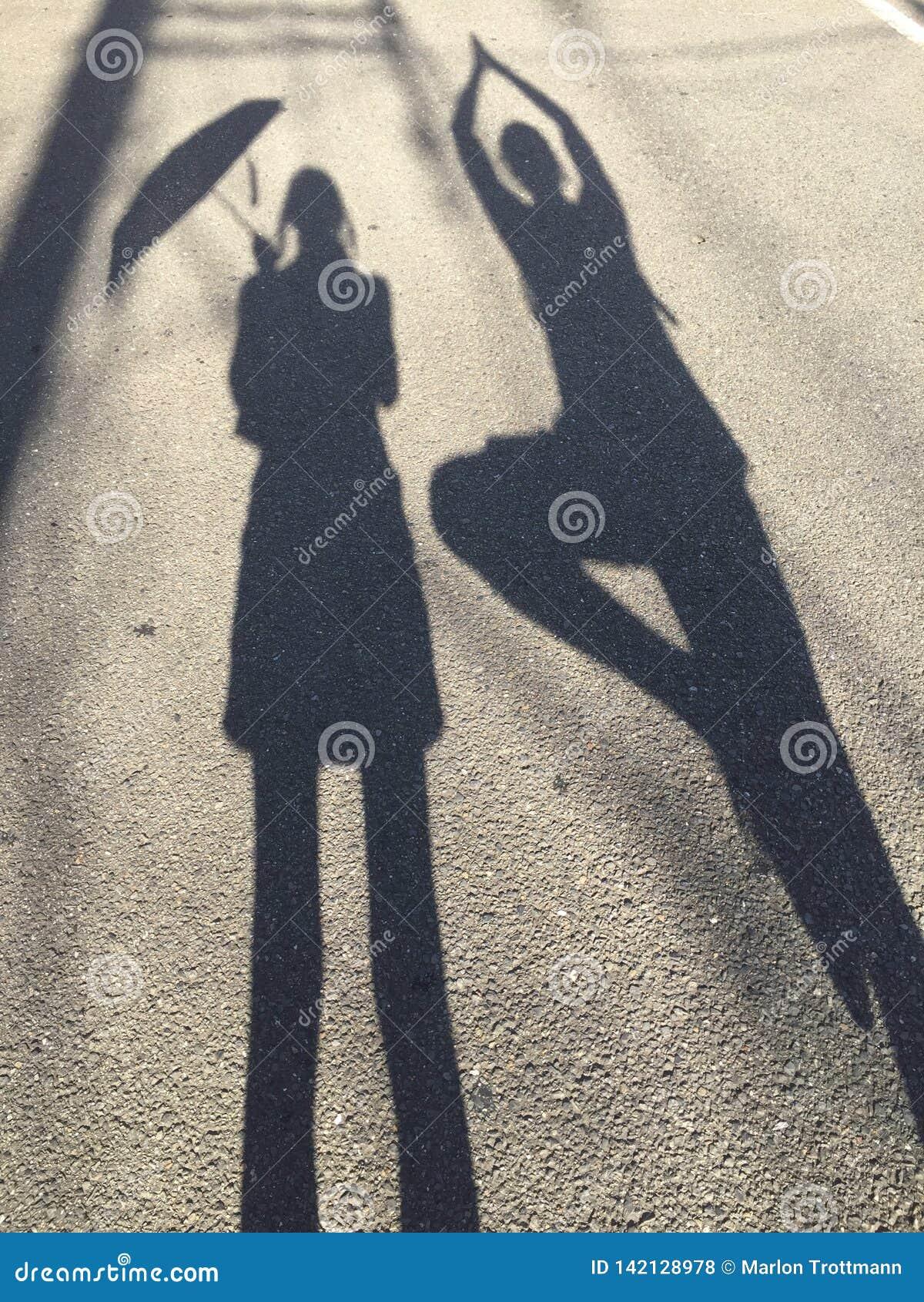 Obrazek kobiety trzyma parasol i mężczyzny robi drzewnej pozie