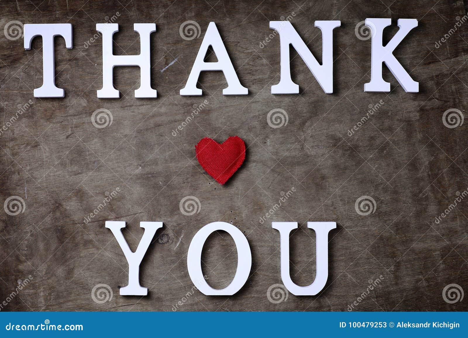 Obrigado exprimir das letras de madeira brancas na tabela e nas mãos