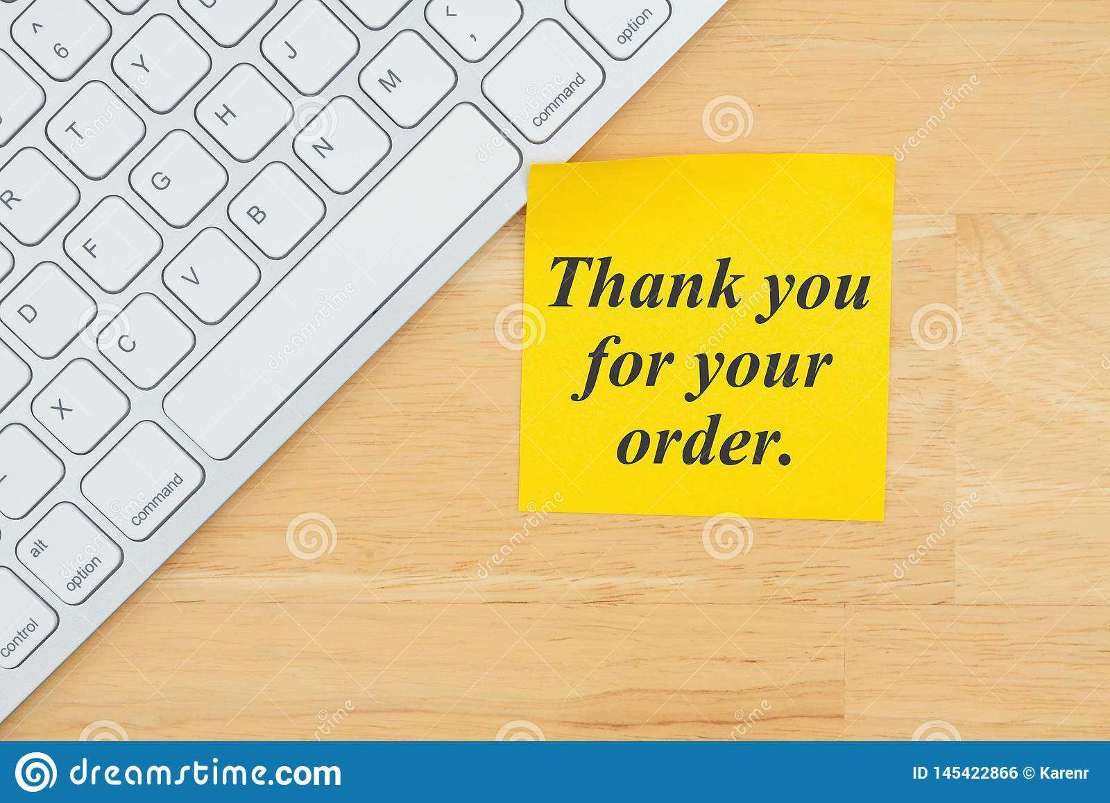 Obrigado para seu texto da ordem em uma nota pegajosa com um teclado