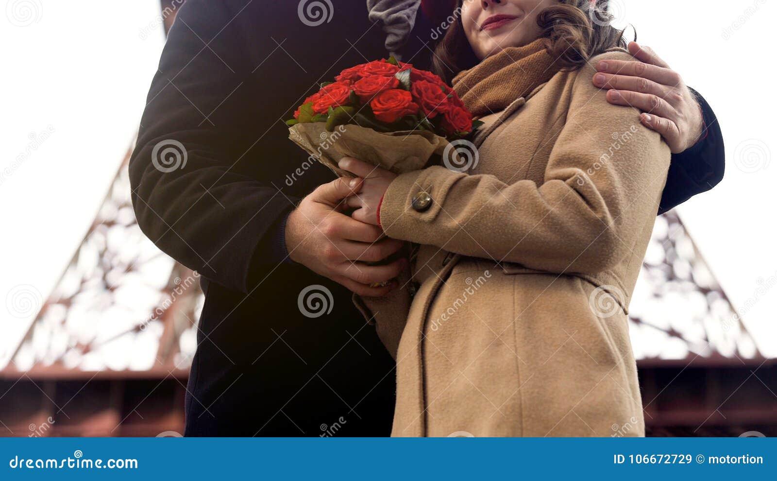 Obsługuje delikatnie ściskać ukochanej kobiety z ładnymi kwiatami w rękach, romans w Paryż