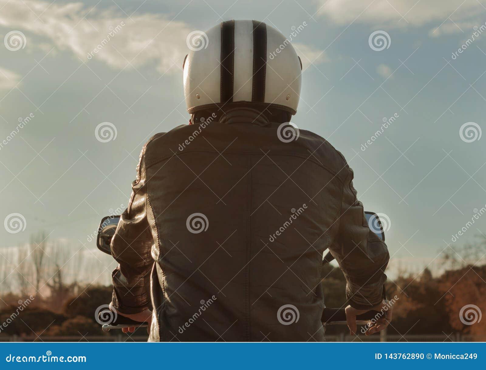 Obsługuje jeździeckiego motocykl z brązu hełmem i skórzaną kurtką