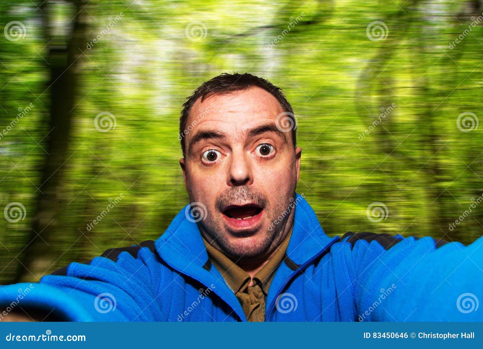 Obsługuje opowiadać selfie ciągnie śmieszną twarz na zamazanym tle