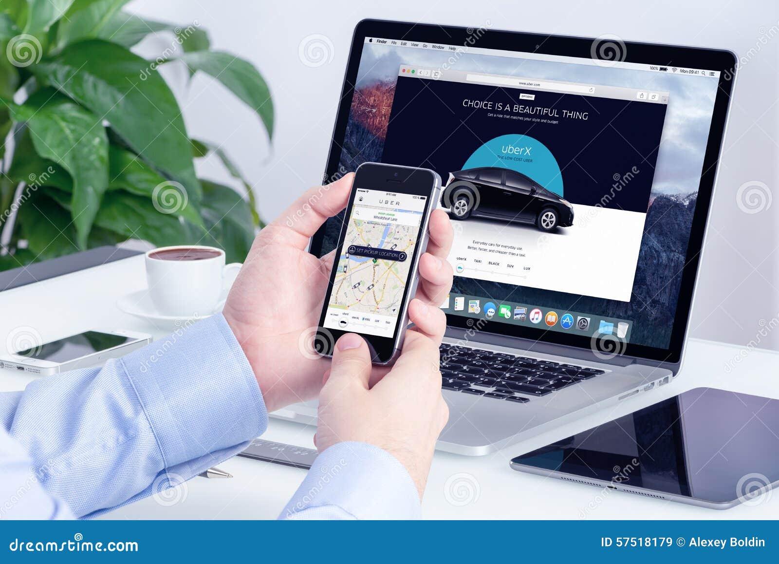Obsługuje rozkazy Uber i Macbook z stroną internetową na tle iPhone