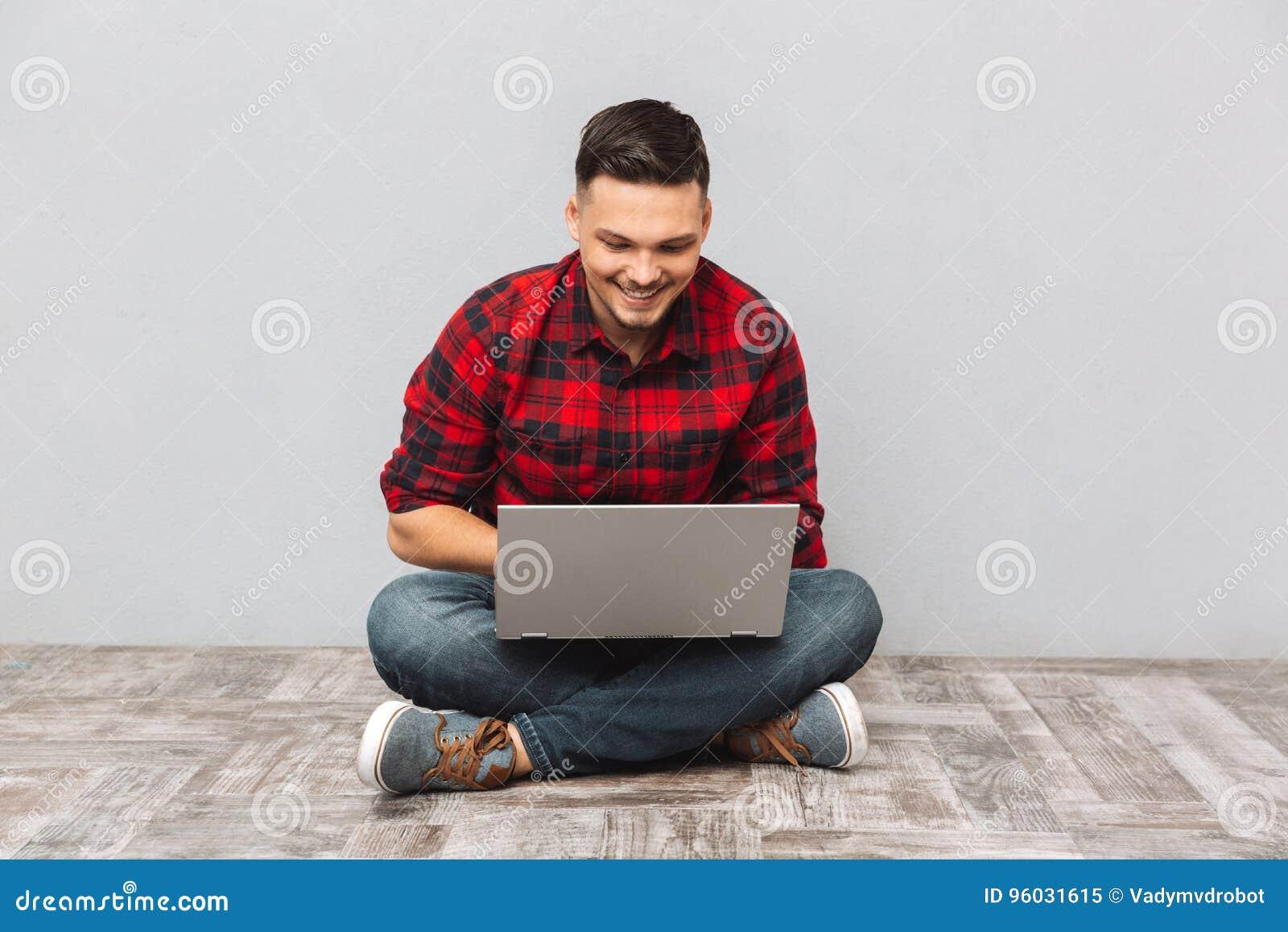 Obsługuje studenckiego działanie na laptopie podczas gdy siedzący na podłoga