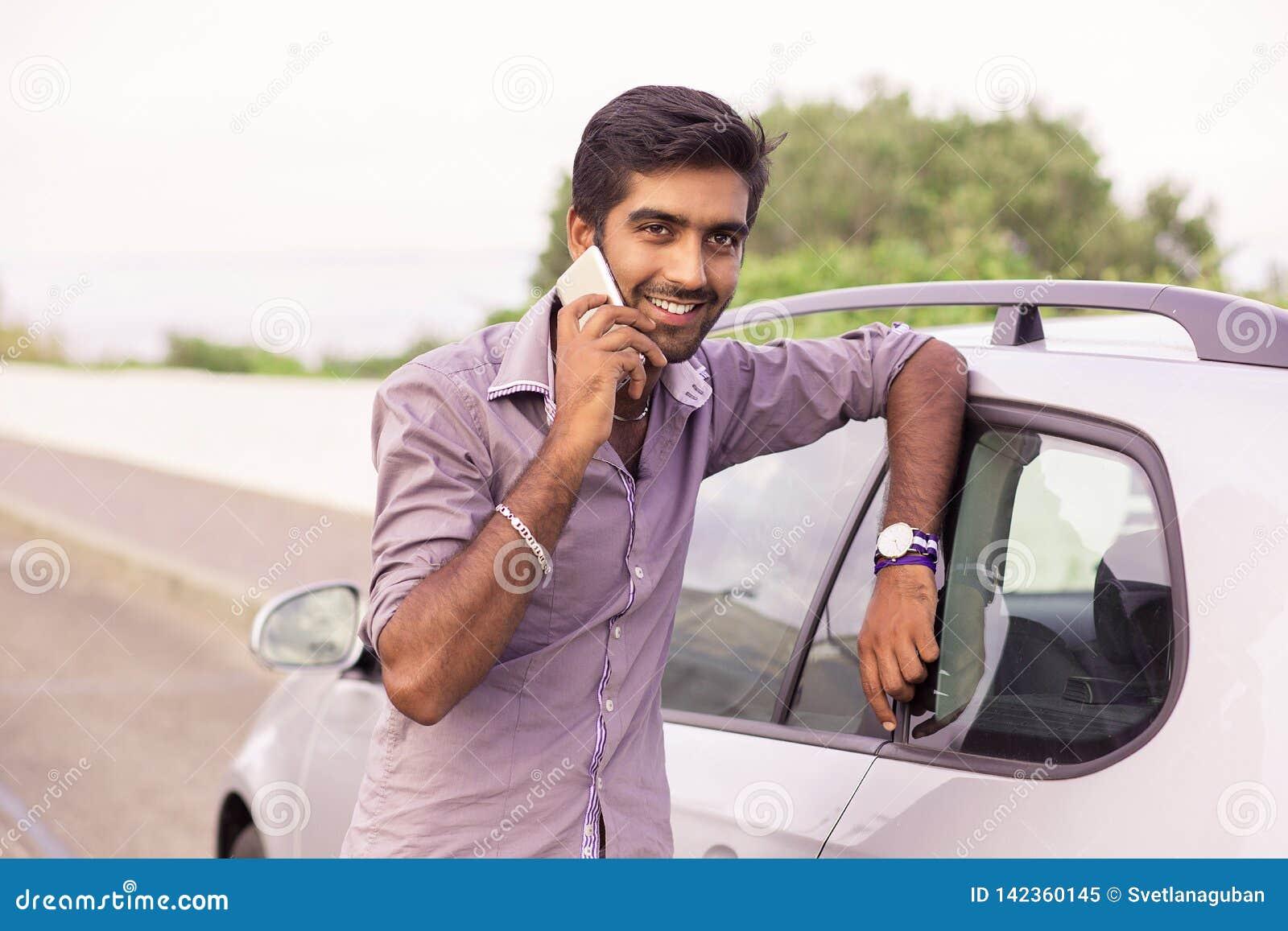 Obsługuje szczęśliwy opowiadać na telefonie opiera na drzwi jego samochód