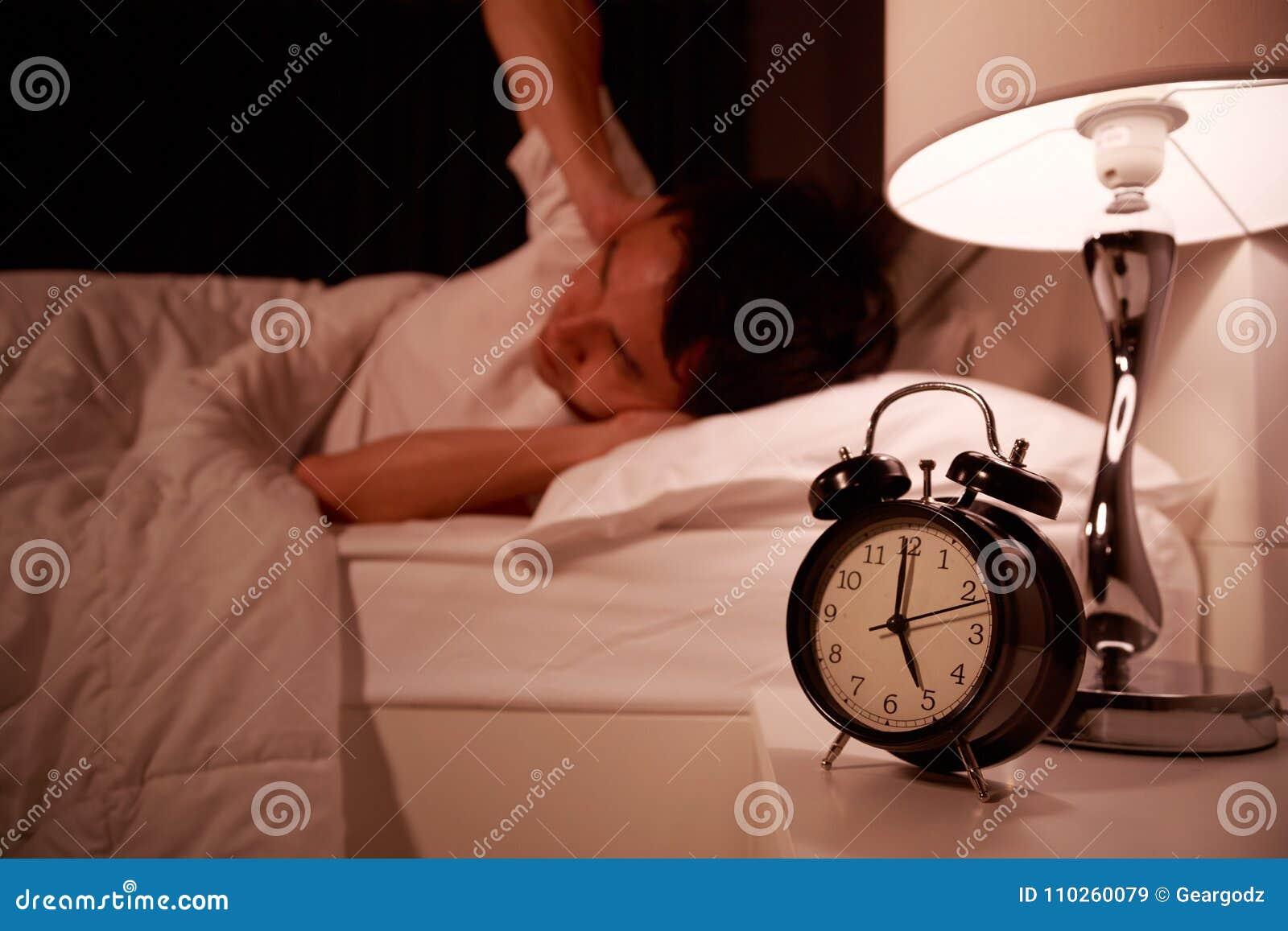 Obsługuje zakończenie ręką od hałasu budzik na łóżku jego ucho