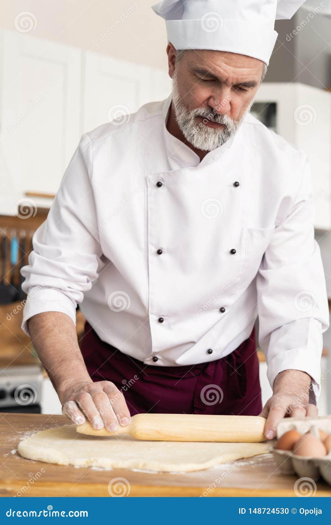 Obs?uguje robi? piekarni w kuchni i tocznemu ciastu na drewnianej tn?cej desce zakrywaj?cej z m?k?