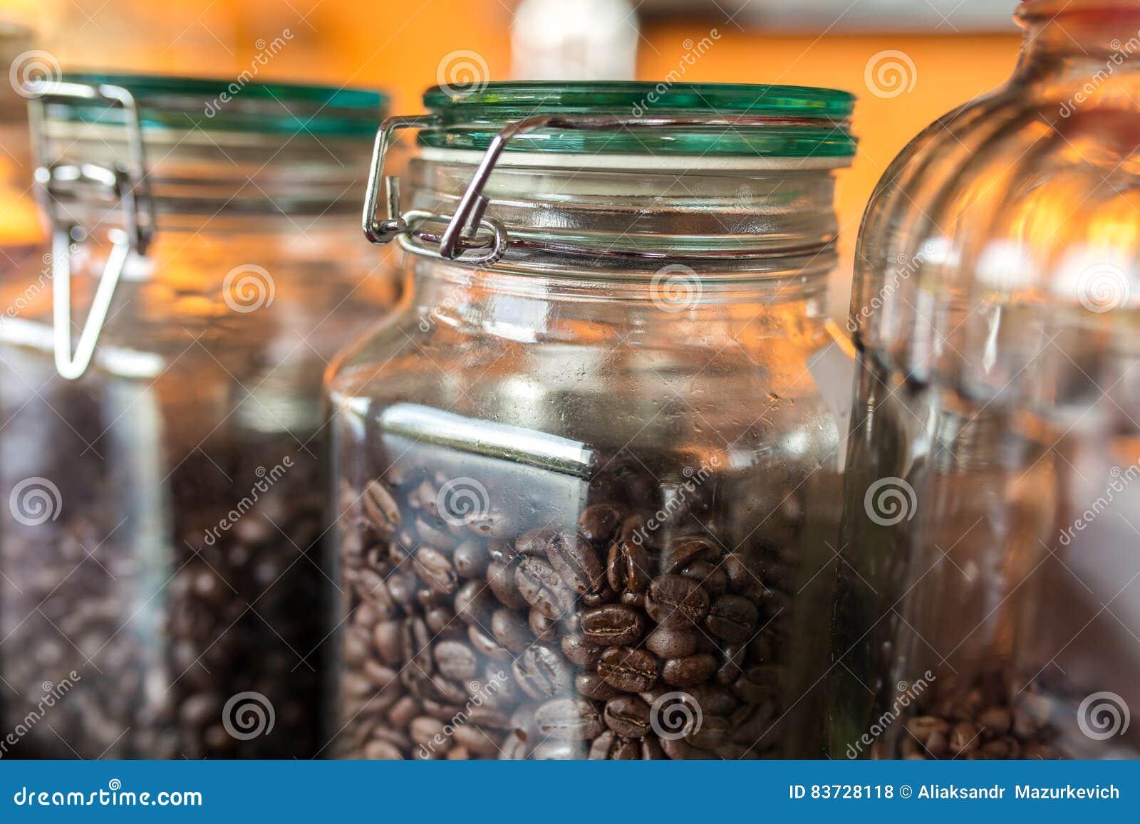 A obscuridade roasted feijões de café em um frasco do vidro