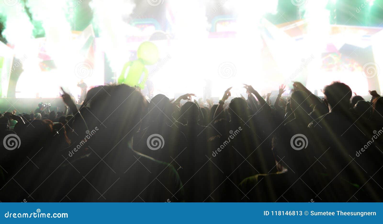 Obscuro das silhuetas da multidão do concerto na ideia traseira do festival