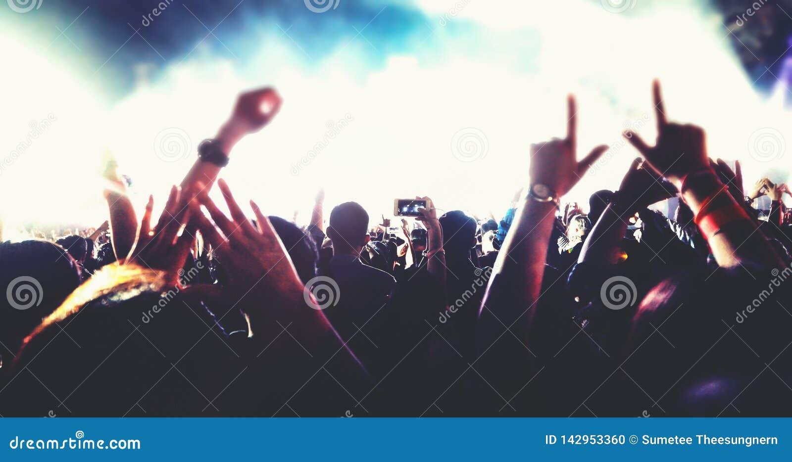 Obscuro das silhuetas da multidão do concerto na opinião traseira a multidão do festival levantar suas mãos na fase brilhante ilu