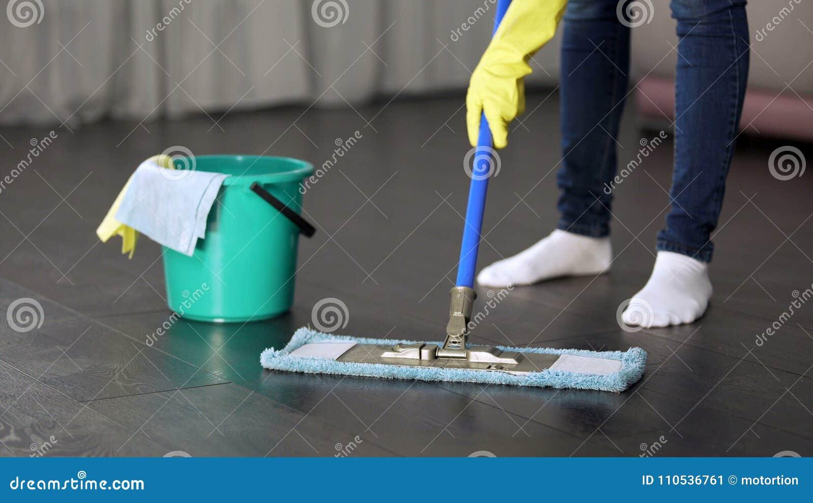 Obsessief met netheids jonge dame die grondig vloer van haar huis wassen