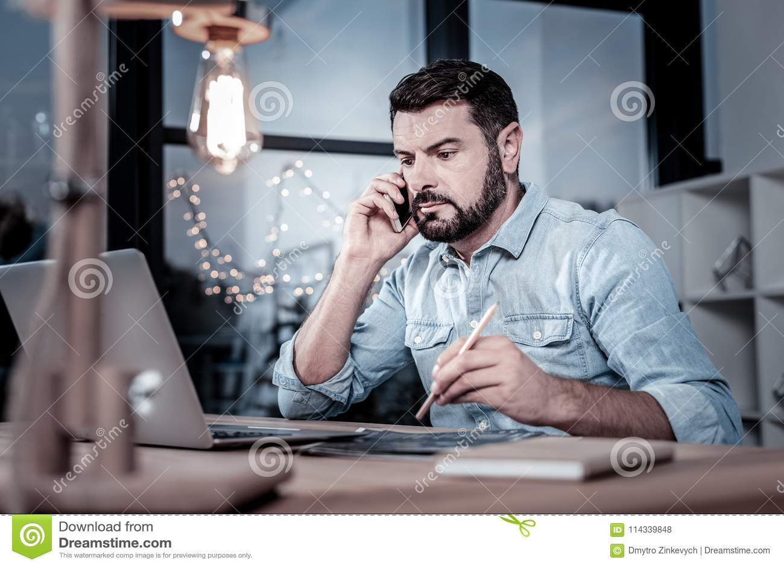 Obsiadły rzetelny pracownik ma rozmowę telefoniczną i używa jego laptop