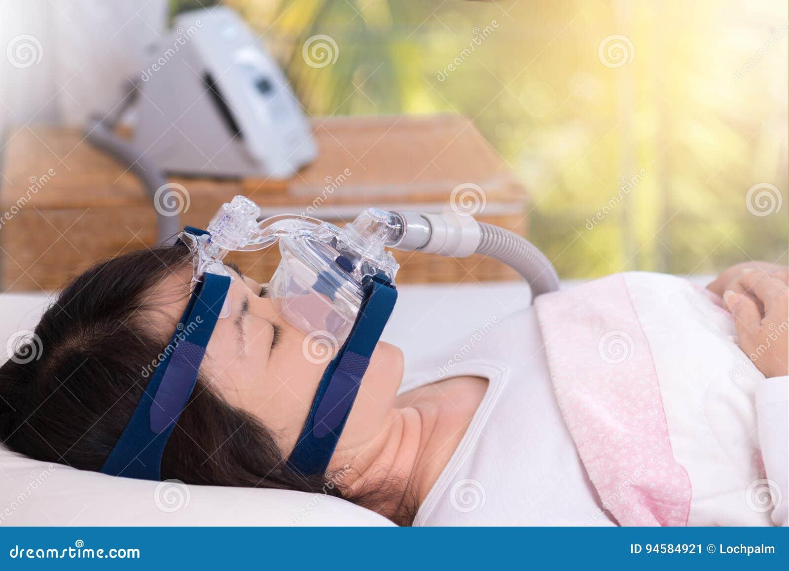 Obstructive sleep apnea therapy, Woman using CPAP machine.