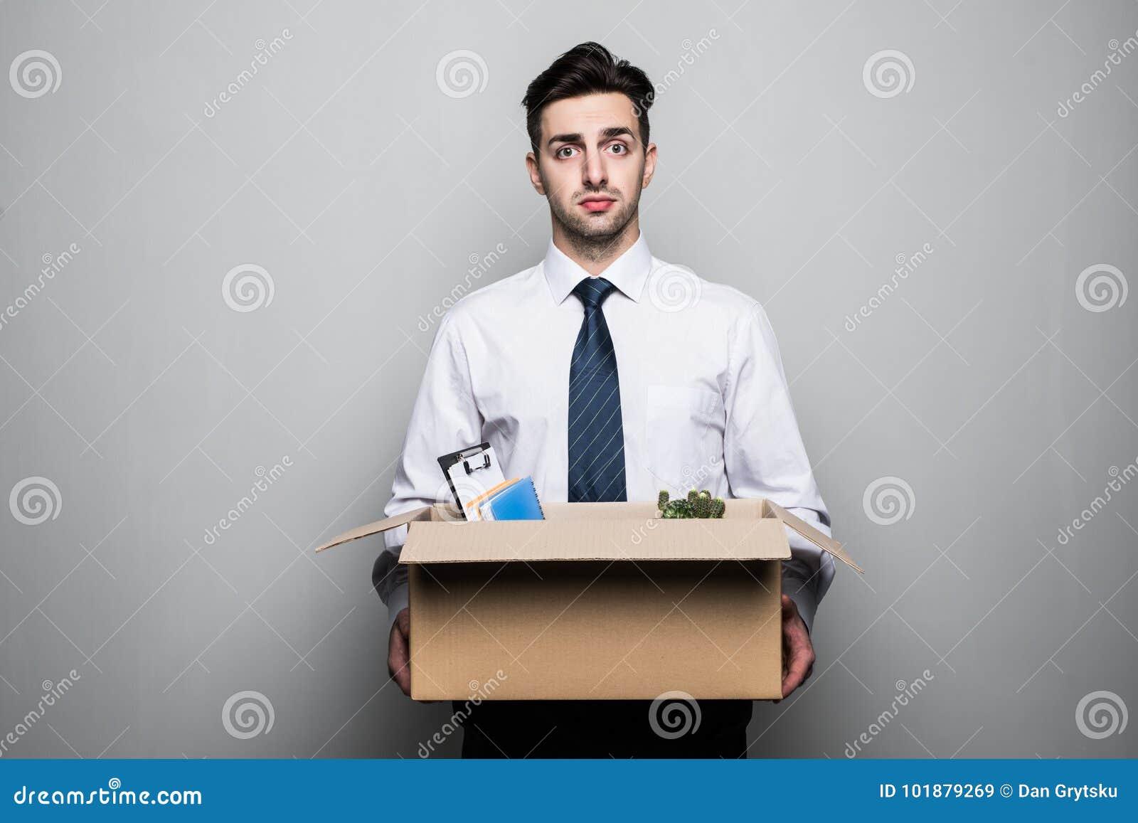 Obtenção despedido Homem de negócios novo considerável no terno no escritório com a caixa com seu material