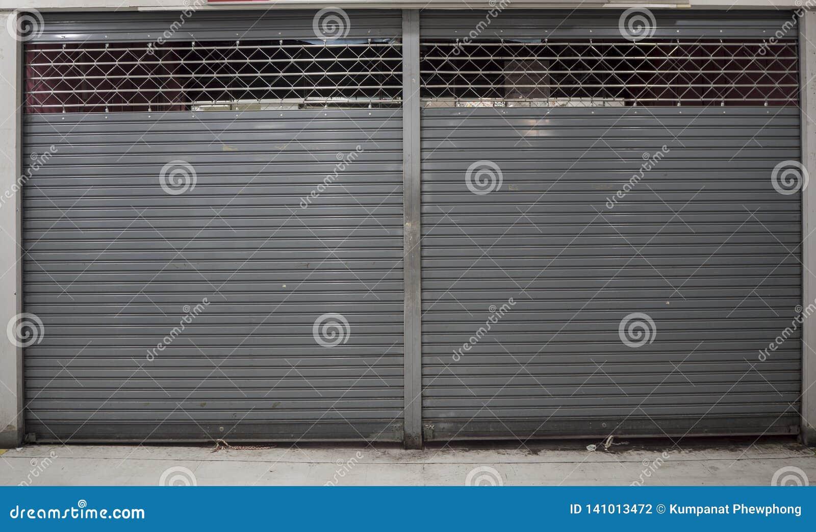 Obturador cercano o puerta rodante del fondo de la tienda con el espacio de la copia