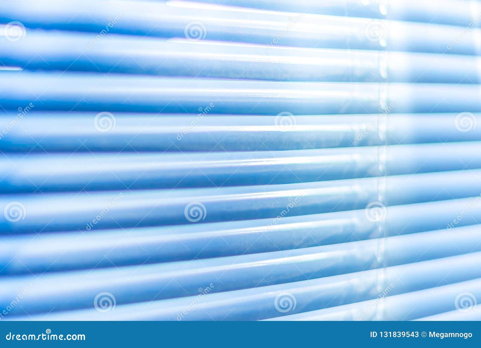 Obturadores azules cerrados, tiro macro Fondo de la persiana Luz del sol a través de persianas horizontales