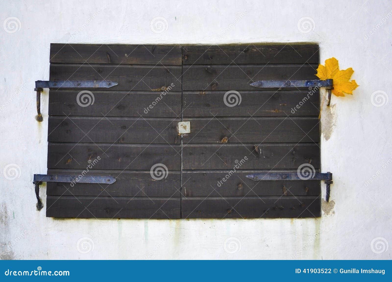 Obturadores viejos rústicos de la ventana en una pared del estuco