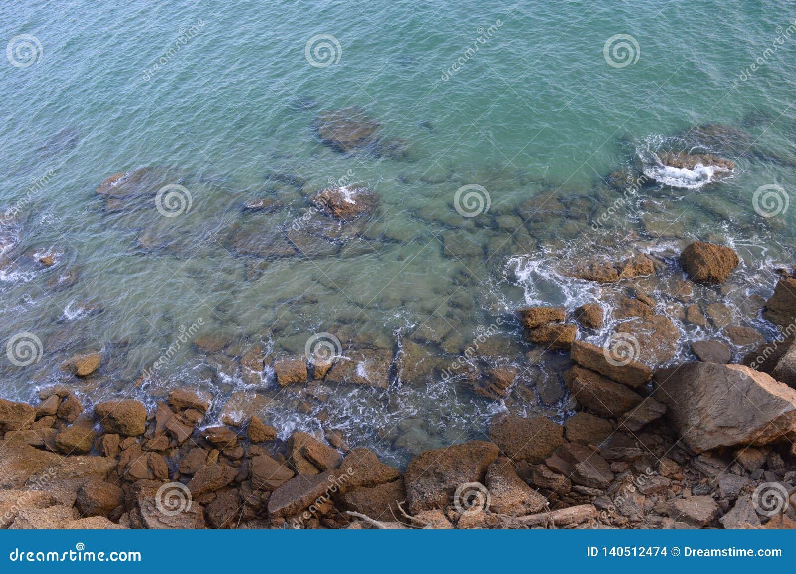 Océan de turquoise et roches brunes