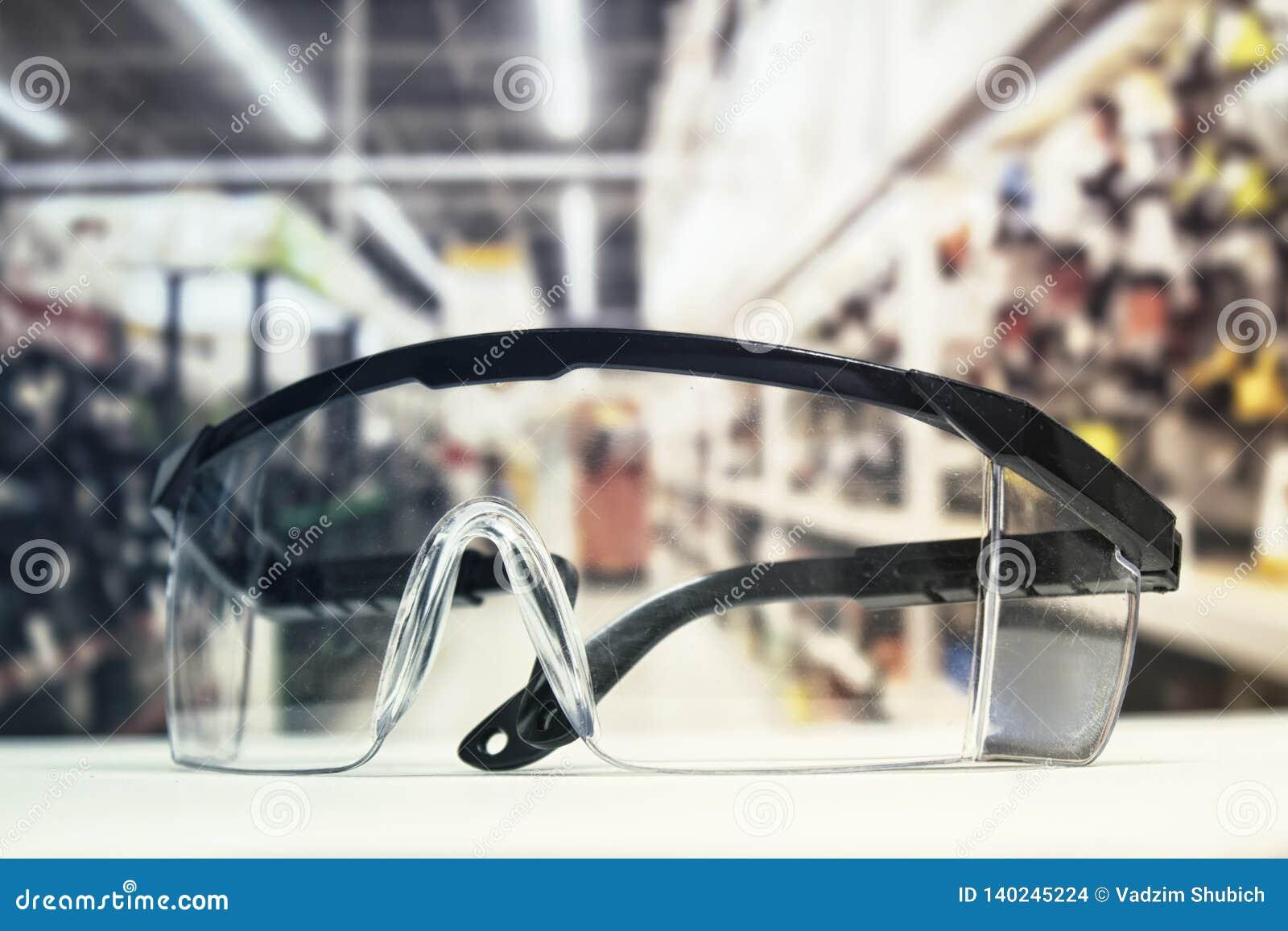 Occhiali di protezione di plastica, sulla tavola e sui precedenti della ferramenta con gli strumenti