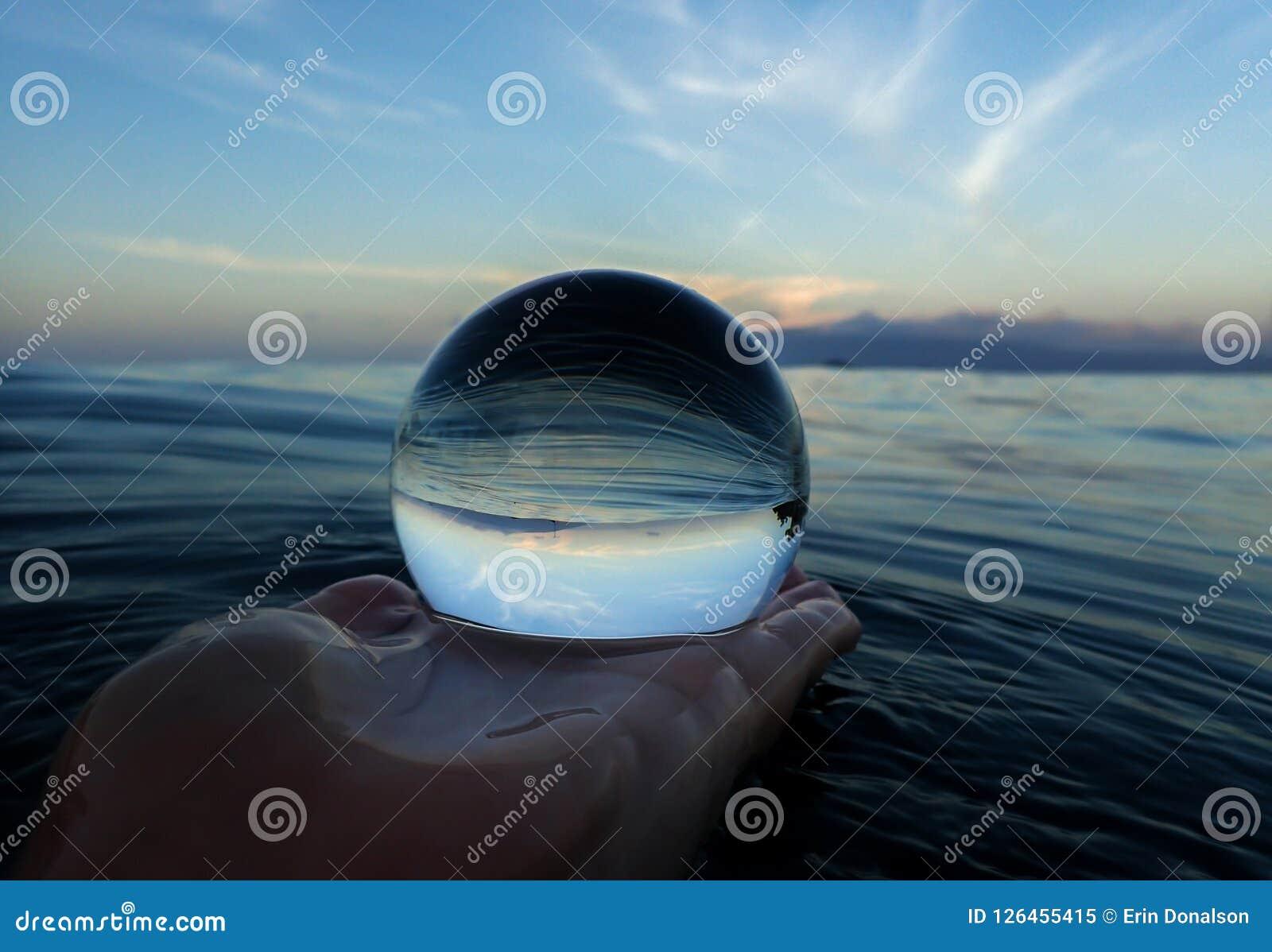 Oceaandieoppervlaktelijnen en texturen met eiland op horizon in bal worden gevangen