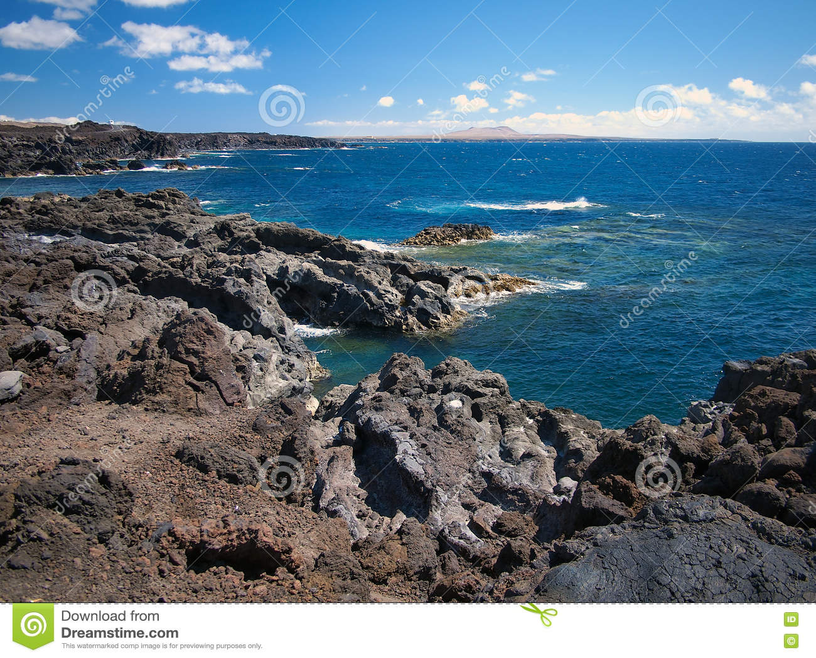 Oceaangolven die op de rotsachtige kust van verharde lava met holen en holten breken Diepe blauwe hemel met witte wolken en berge