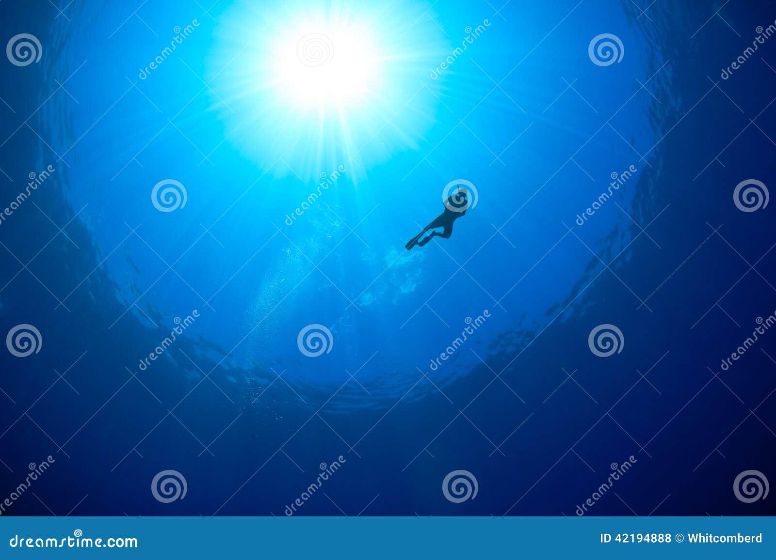 Oceaanoppervlaktezonnestraal met snorkellersilhouet