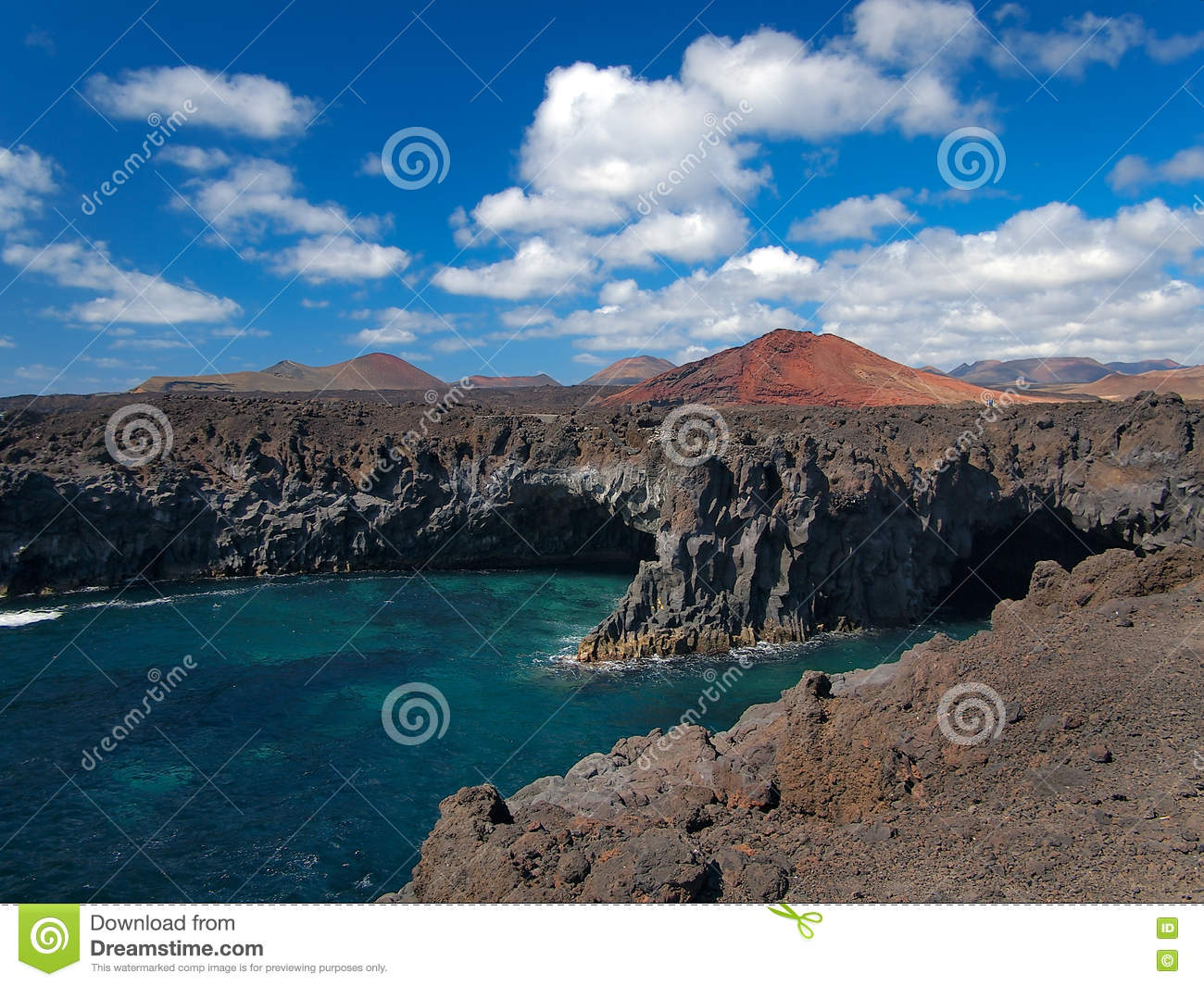 Ocean waves breaking on the rocky coast of hardened lava with caverns and cavities. Deep blue sky with white clouds and mountains