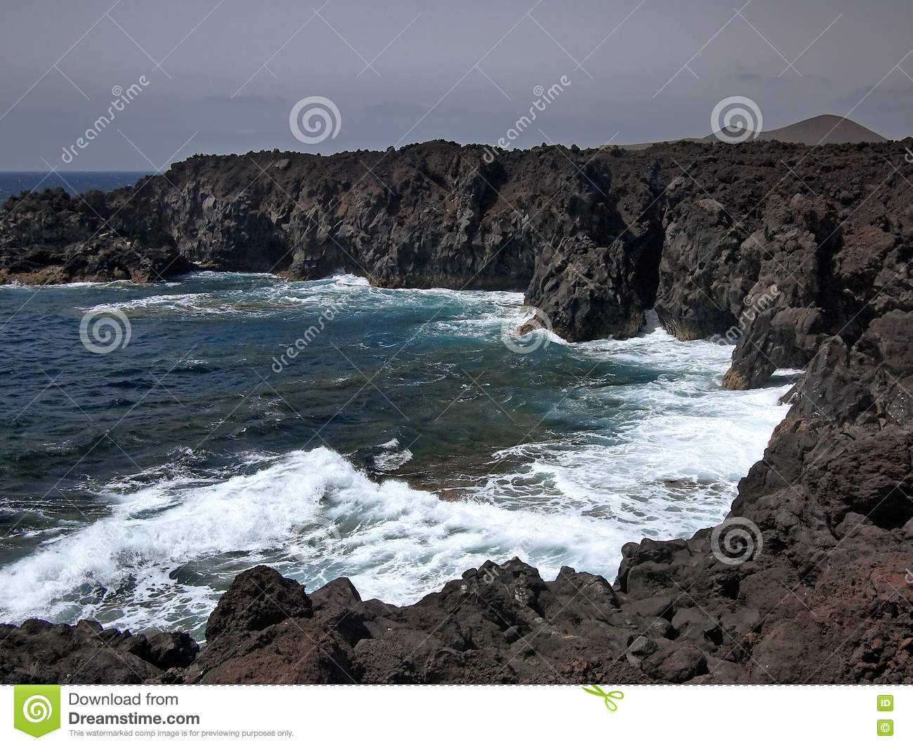 Ocean waves breaking on the rocky coast of hardened lava with caverns and cavities. Mountains and volcanoes on the horizon