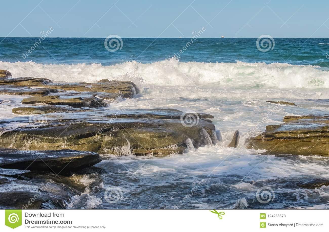 Ocean waves crash against eons old volcanic rock and water runs and breaks the stone - with tiny boats on the horizon