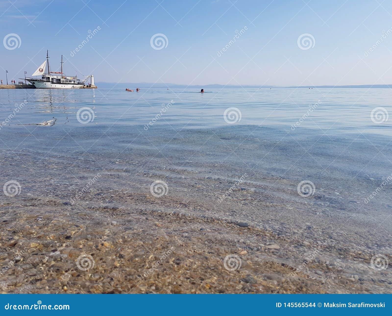 Oceano calmo na manhã com o barco na natação do porto e dos povos