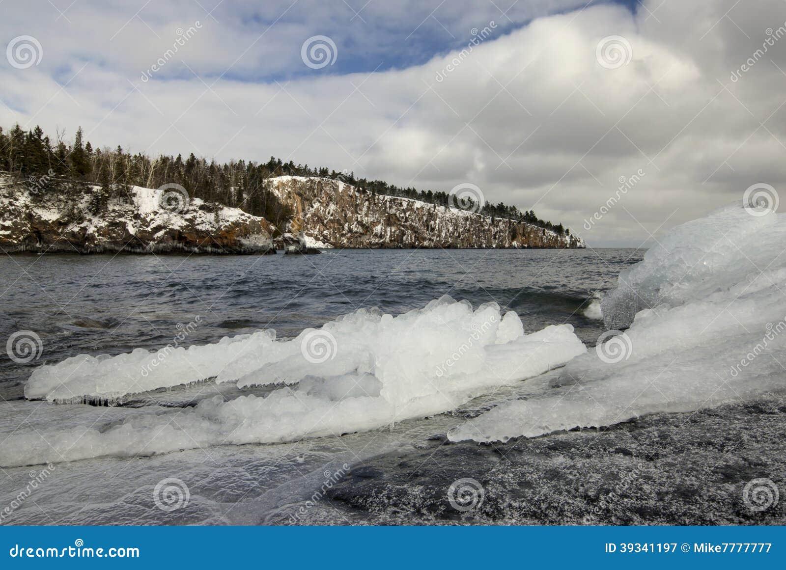 Is och snö på kusten av Lake Superior, skyffelpunkt i avståndet.