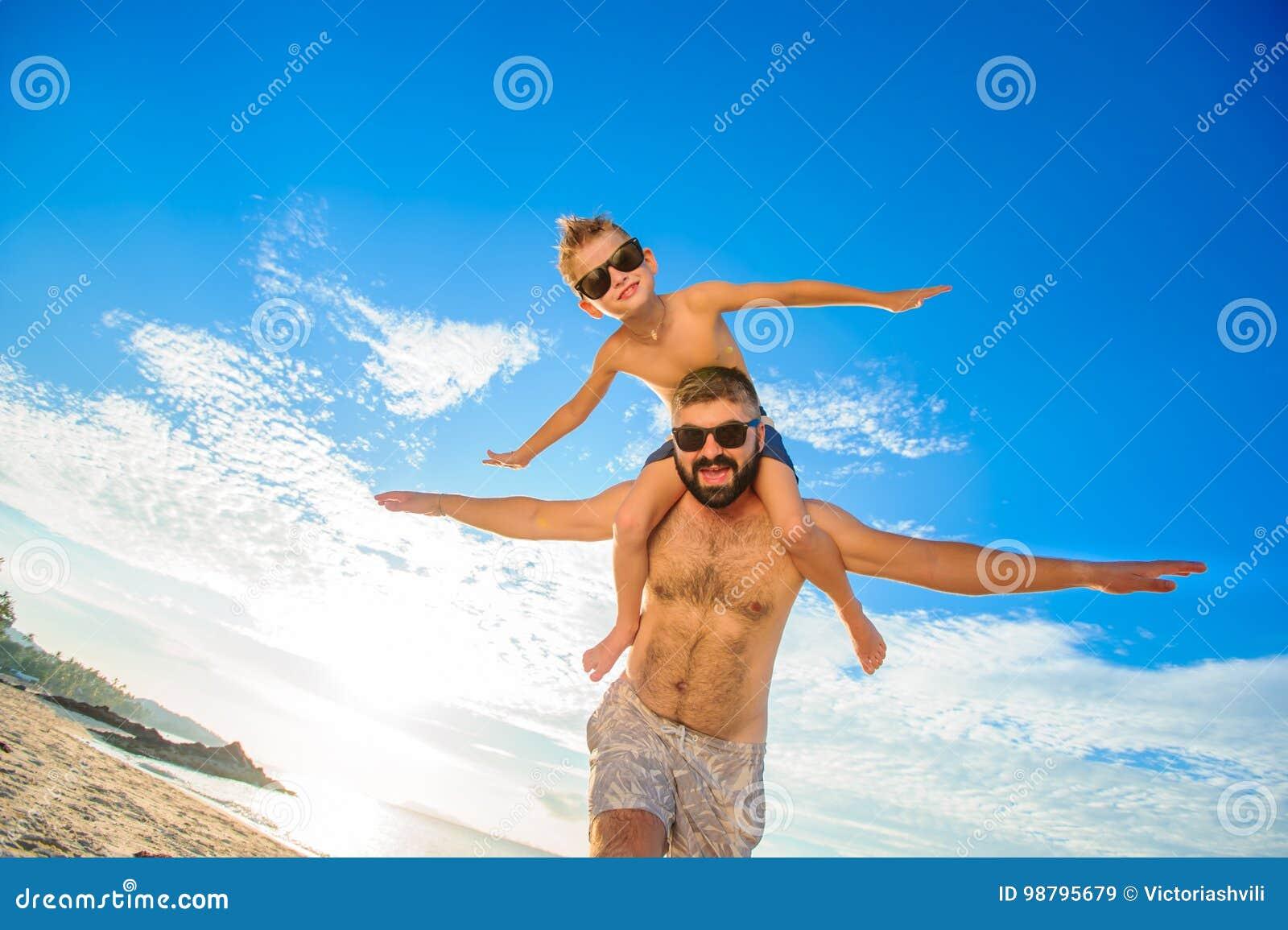 Ocho años del muchacho que se sienta en el ` s del papá llevan a hombros Ambos en pantalones cortos y gafas de sol de la natación