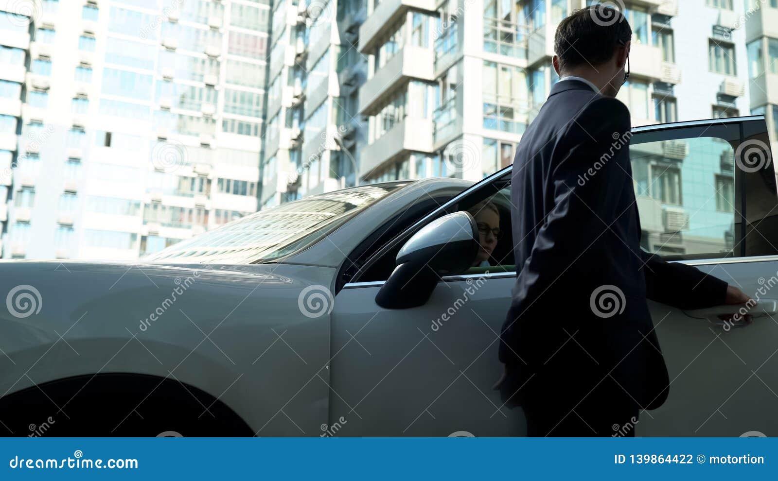 Ochroniarz otwiera samochodowych drzwi bizneswoman, zapewnia ochronę dla vip osoby