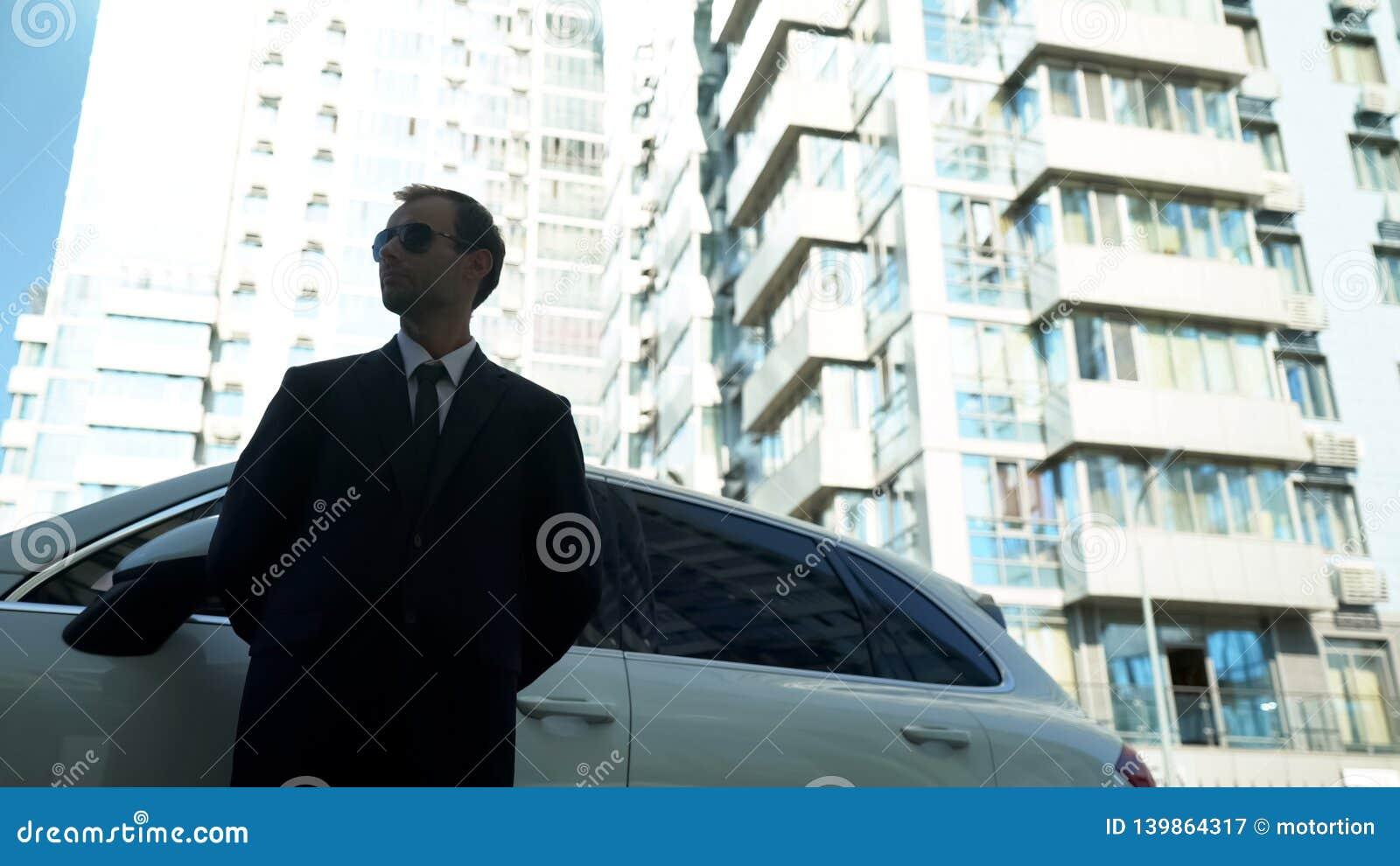 Ochroniarz stoi blisko biznesowego samochodu, sprawdza bezpieczeństwo i ochrona, dolnego widok,