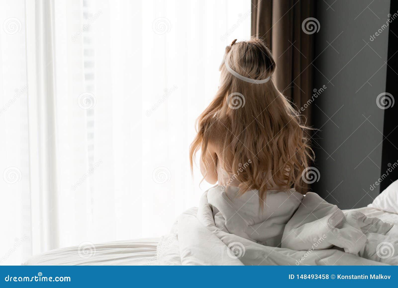 Ochtend in hotelruimte De jonge vrouw zit op comfortabel bed in masker voor het slapen op hoofd Groot venster op achtergrond