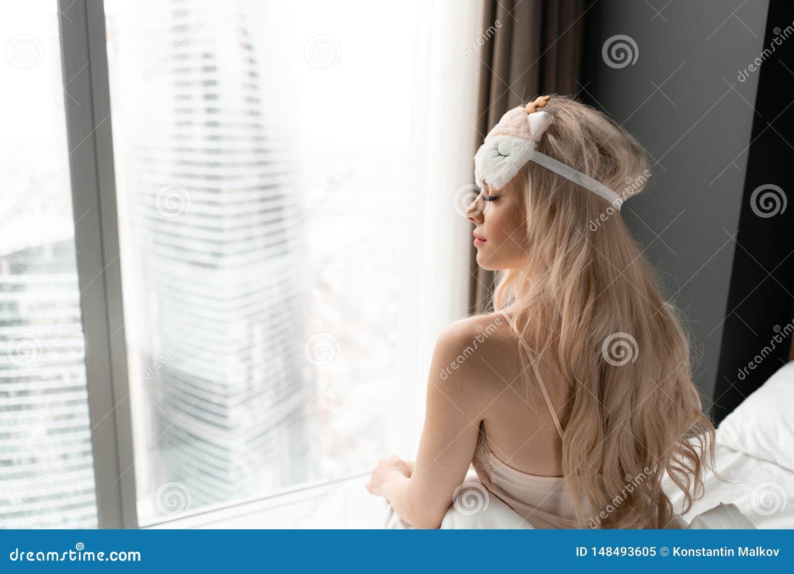 Ochtend in hotelruimte De jonge vrouw zit op comfortabel bed in masker voor het slapen op hoofd Venster van een wolkenkrabber
