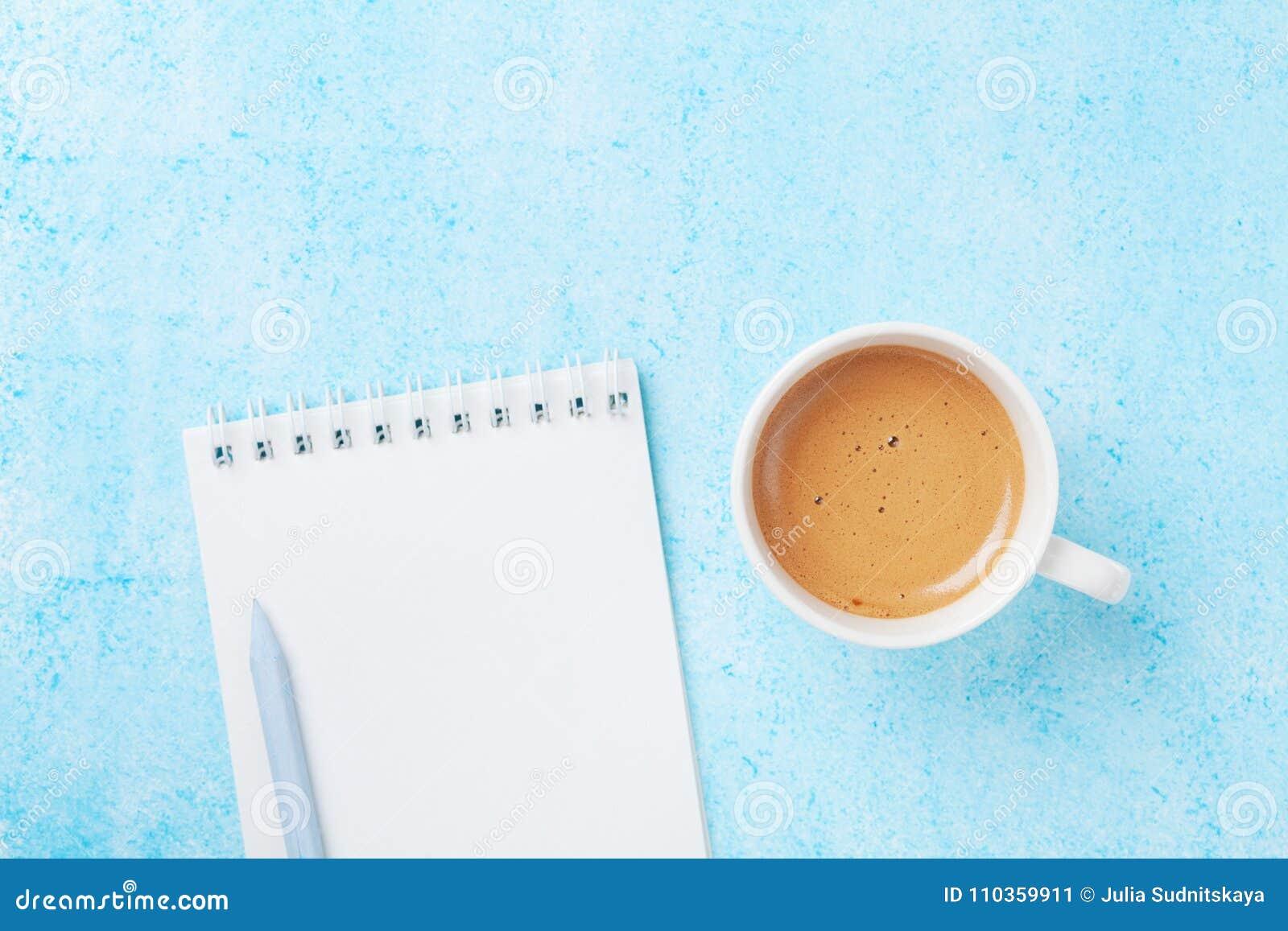Ochtendkoffie, potlood en schoon notitieboekje op blauwe de bovenkantmening van de pastelkleurlijst vlak leg stijl Planning en on